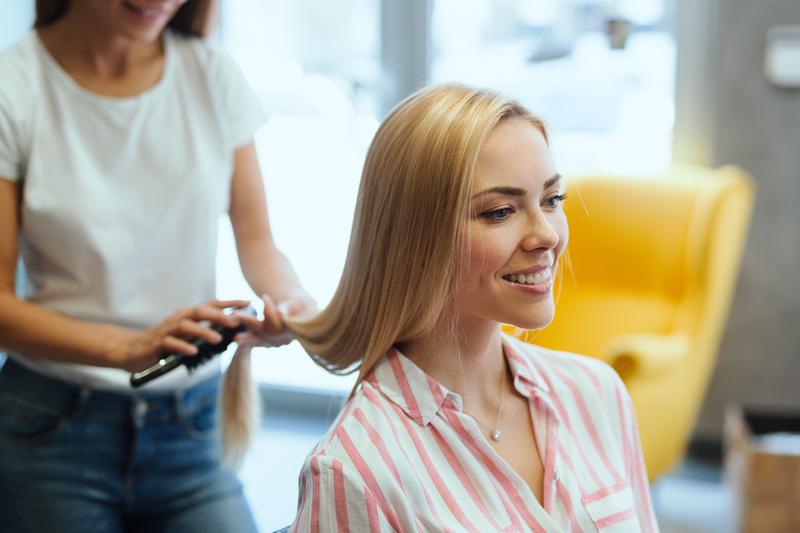 hairdresser cutting womans hair in salon