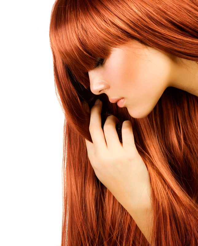 image of woman looking down with vibrant ginger hair